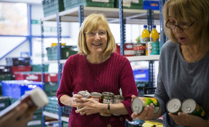warehouse volunteers chatting about tinned food